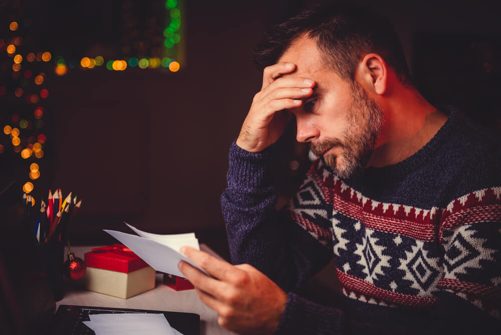 Man stressed over holiday debt.