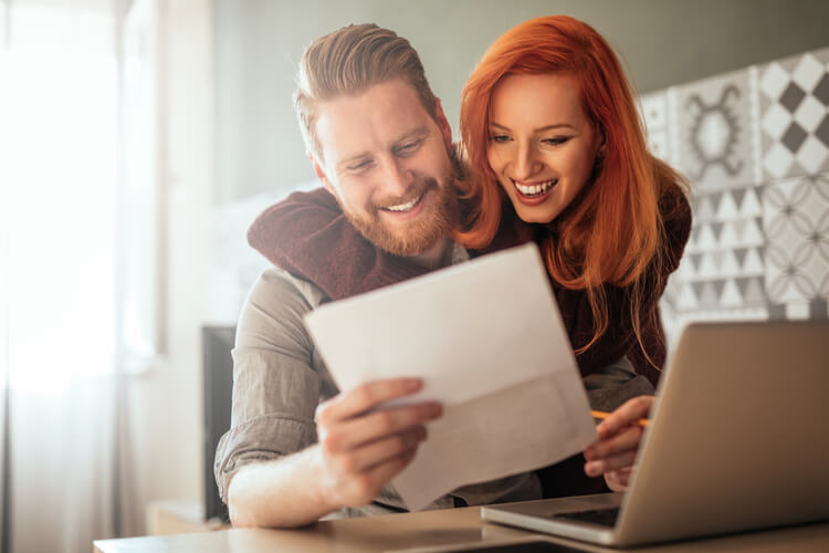 title loans near me survivors guide happy couple with bills at couple